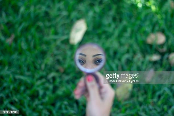 reflection of woman in hand mirror on plants - hand mirror stock photos and pictures