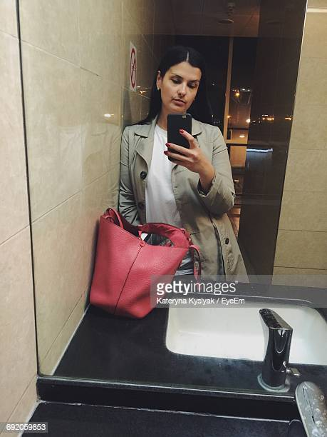 reflection of woman in mirror leaning on wall while holding mobile phone in public restroom - femme wc photos et images de collection