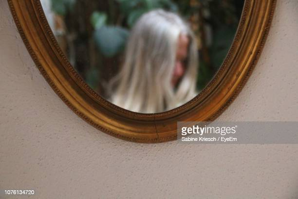 reflection of woman in mirror - sabine kriesch stock-fotos und bilder