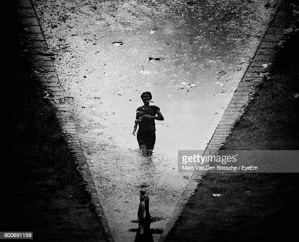 Reflection Of Woman In Puddle On Street