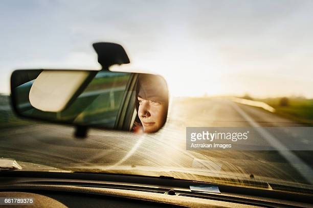Reflection of woman in rear-view mirror