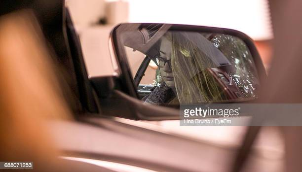 Reflection Of Woman In Side-View Mirror