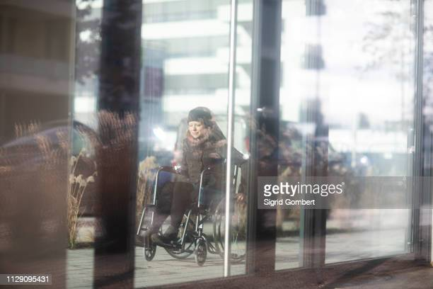 reflection of woman in wheelchair on glass windows of building - sigrid gombert imagens e fotografias de stock