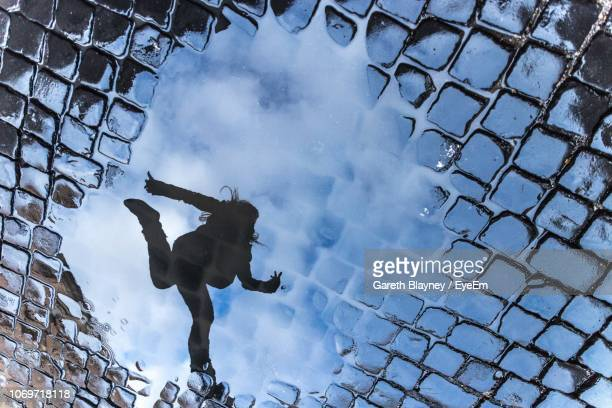 reflection of woman jumping seen in puddle on street - puddle stock pictures, royalty-free photos & images