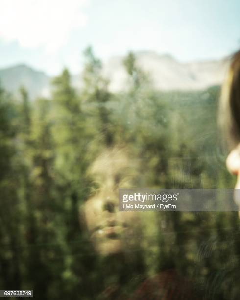 Reflection Of Woman On Bus Window Against Trees