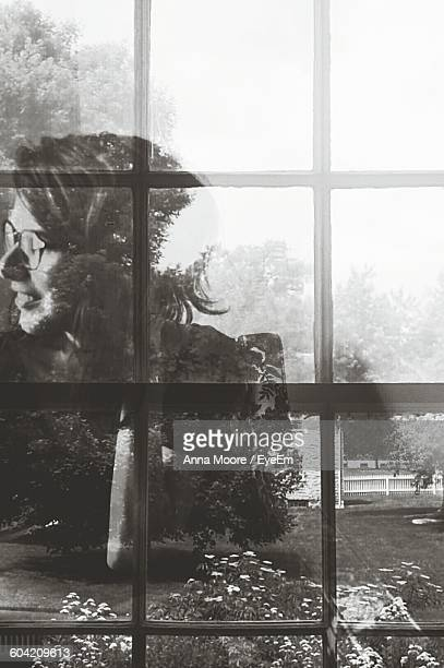 Reflection Of Woman On Glass Window