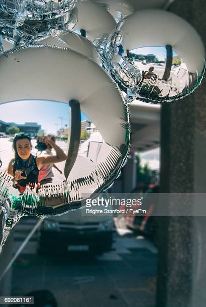 Reflection Of Woman On Helium Balloon While Photographing Using Camera