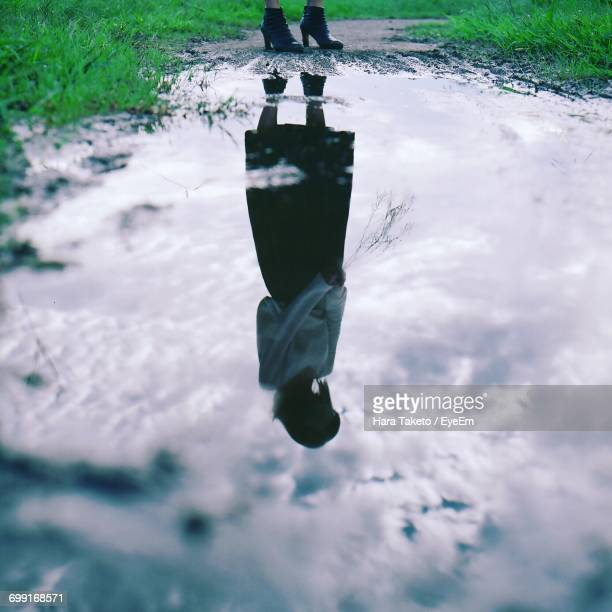 Reflection Of Woman On Puddle