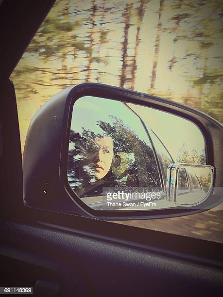 Reflection Of Woman On Side-View Mirror