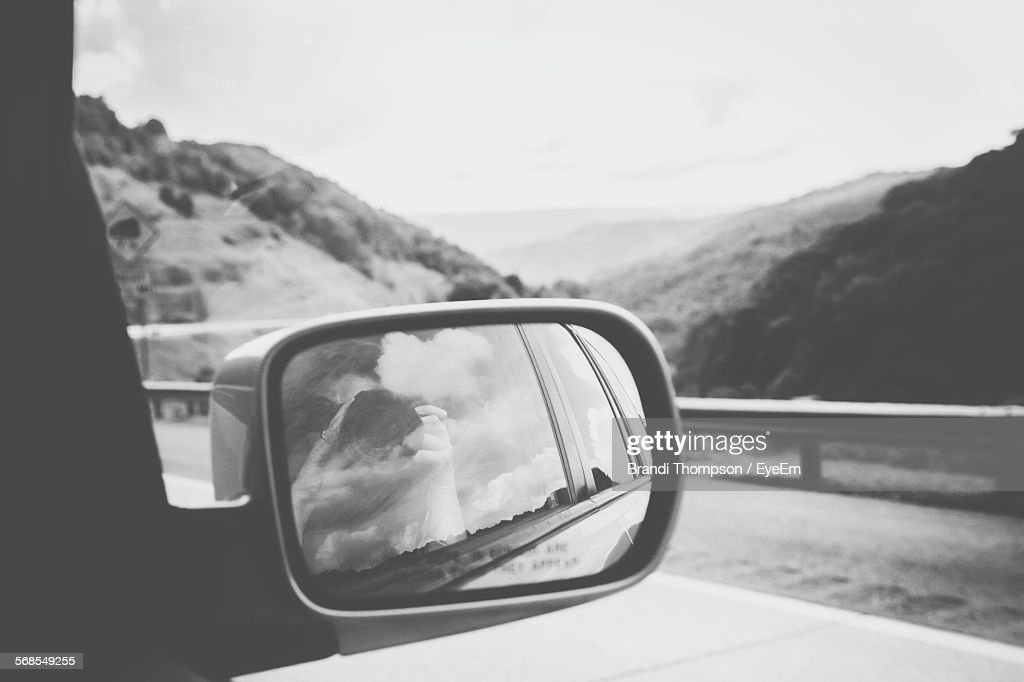 Reflection Of Woman Photographing On Car Rear-View Mirror : Stock Photo
