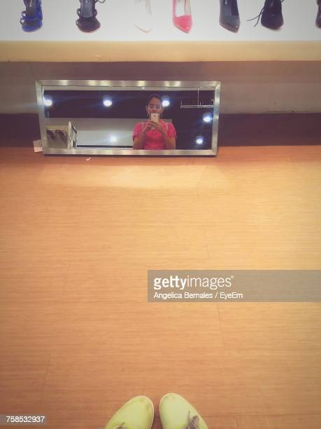 Reflection Of Woman Photographing On Mirror In Store