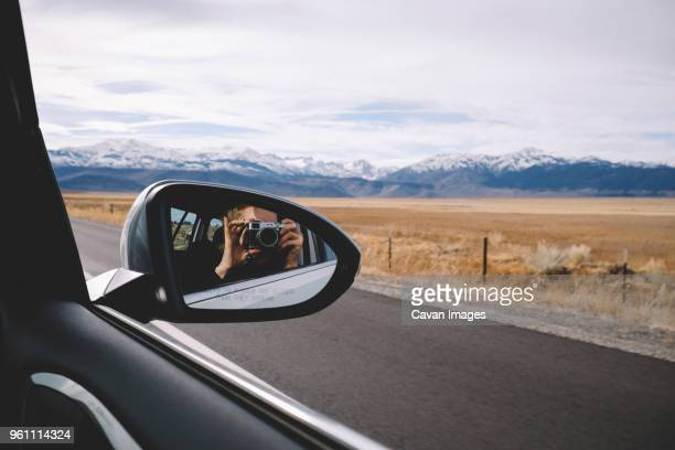 reflection of woman photographing seen in side-view mirror against mountains and cloudy sky - vehicle mirror stock photos and pictures