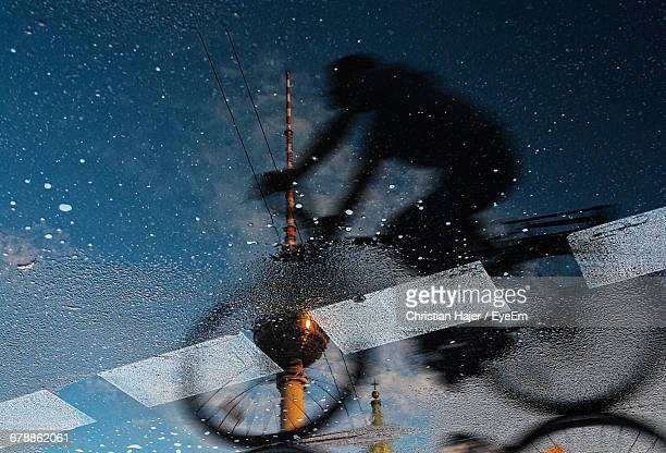 Reflection Of Woman Riding Bicycle And Fernsehturm On Puddle At Street