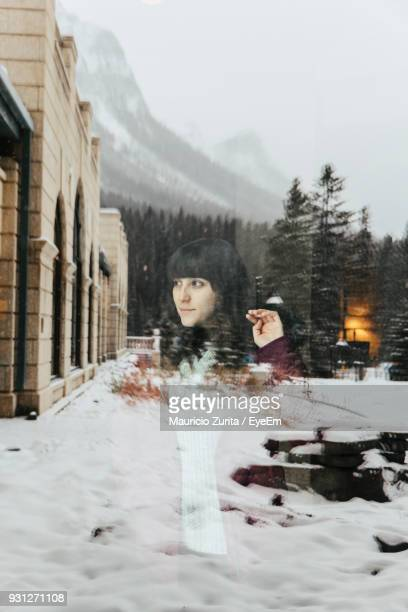 Reflection Of Woman Seen On Glass Window During Winter