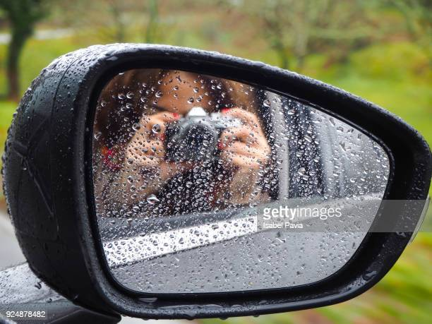 Reflection of woman selfie in side-view mirror of car