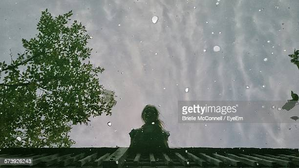 reflection of woman standing at bridge on river - mcconnell stock pictures, royalty-free photos & images
