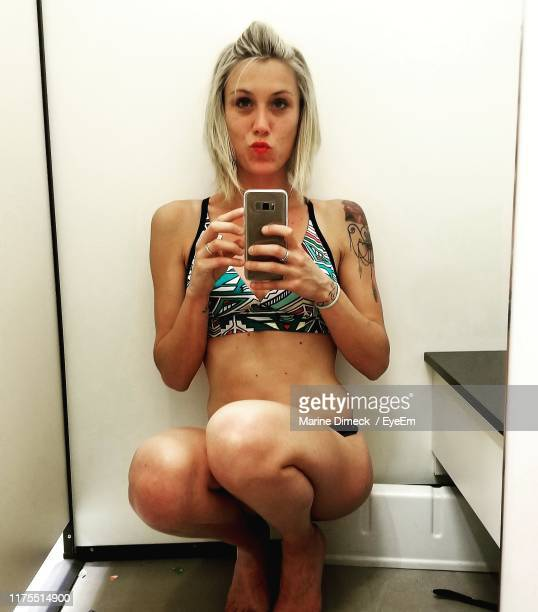 reflection of woman taking selfie in mirror at home - mirror selfie stock pictures, royalty-free photos & images