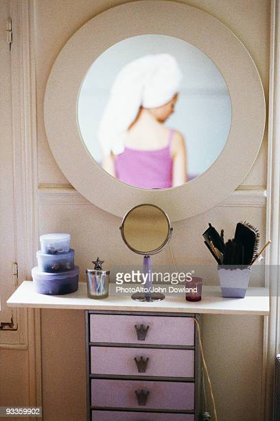 Reflection of woman with head wrapped in towel in mirror hanging above woman's dressing table