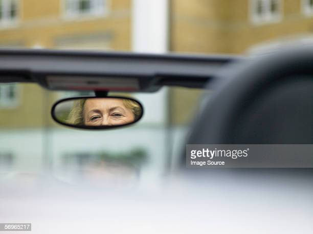 Reflection of woman's eyes in rear view mirror