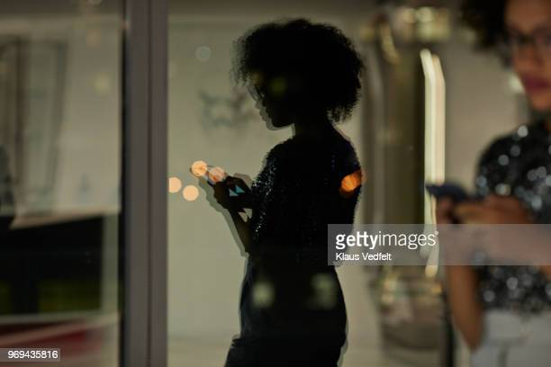 reflection of young businesswoman checking smartphone in the office at night - licht natuurlijk fenomeen stockfoto's en -beelden