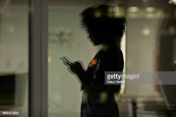 reflection of young businesswoman checking smartphone in the office at night - digital native stock-fotos und bilder