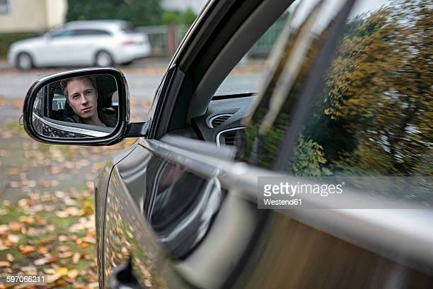 Reflection of young man in wing mirror