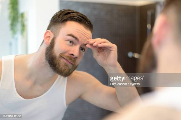 reflection of young man tweezing eyebrows on mirror in bathroom - epilation maillot photos et images de collection