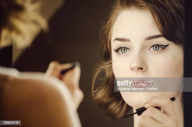 reflection of young woman applying eyeliner in mirror - eye liner stock photos and pictures