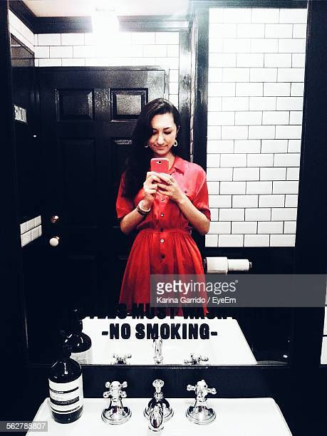 Reflection Of Young Woman Clicking Photograph In Bathroom