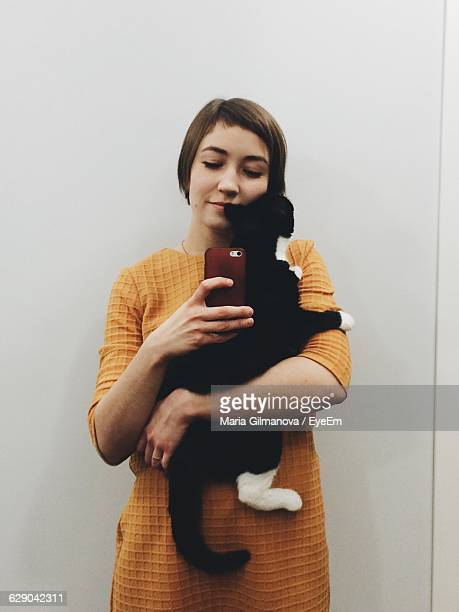Reflection Of Young Woman Holding Cat And Clicking Photograph With Smart Phone