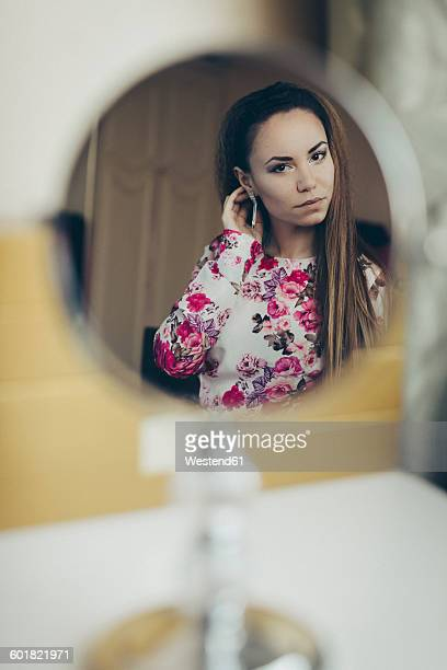 Reflection of young woman in floral dress in mirror