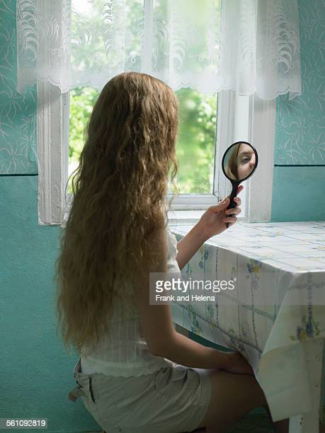 Reflection of young woman looking in hand mirror in kitchen