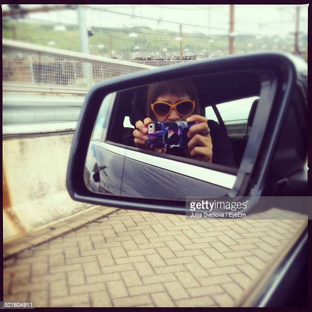 Reflection Of Young Woman On Side-View Mirror Taking Self Portrait In Car