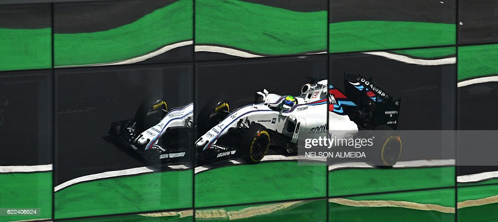 TOPSHOT - Reflection on a glass panel by the track of Brazilian Formula One driver Felipe Massa powering his Williams in the Interlagos racetrack on November 11, 2016 in Sao Paulo, Brazil, on the second free practice for the Brazilian Formula One GP on November 13th / AFP / NELSON