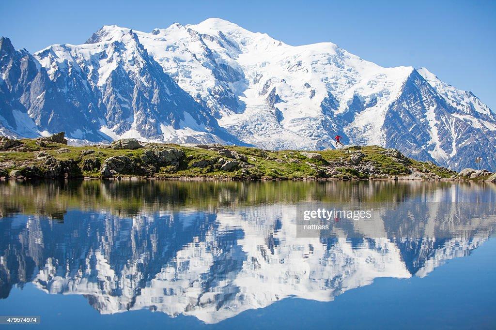 Reflejo en crystal clear lake, hombre corriendo alpino : Foto de stock
