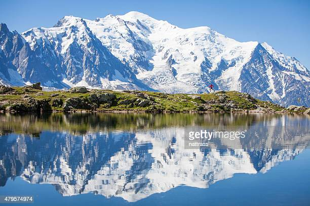reflection on crystal clear alpine lake, running man - mont blanc massif stock photos and pictures