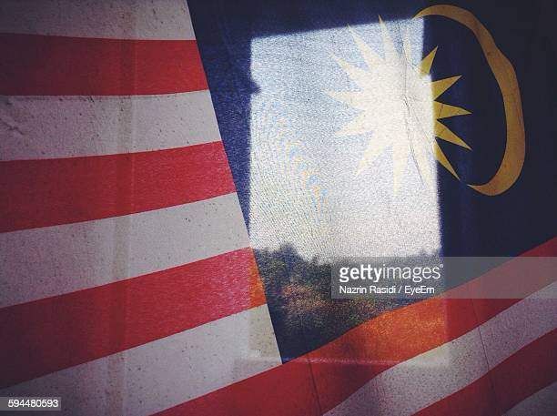 Reflection On Glass Window Against Malaysia Flag