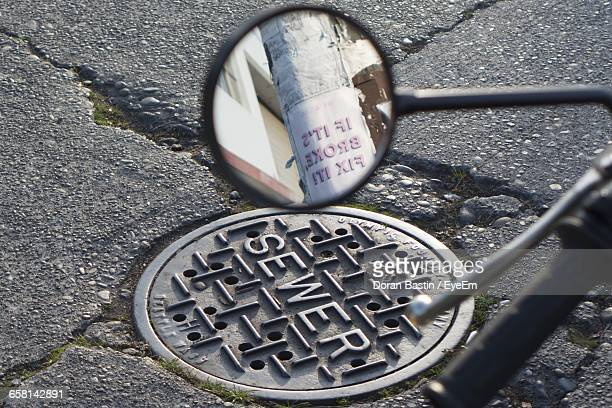 Reflection On Round Mirror Against Manhole