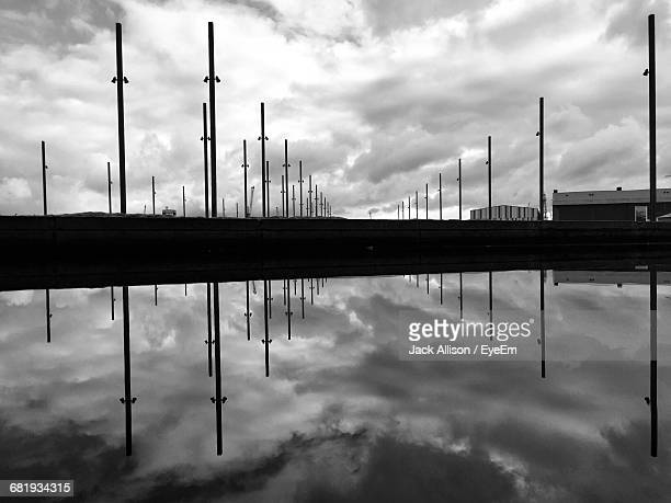 Reflection On Silhouette Poles And Clouds On Calm Pond