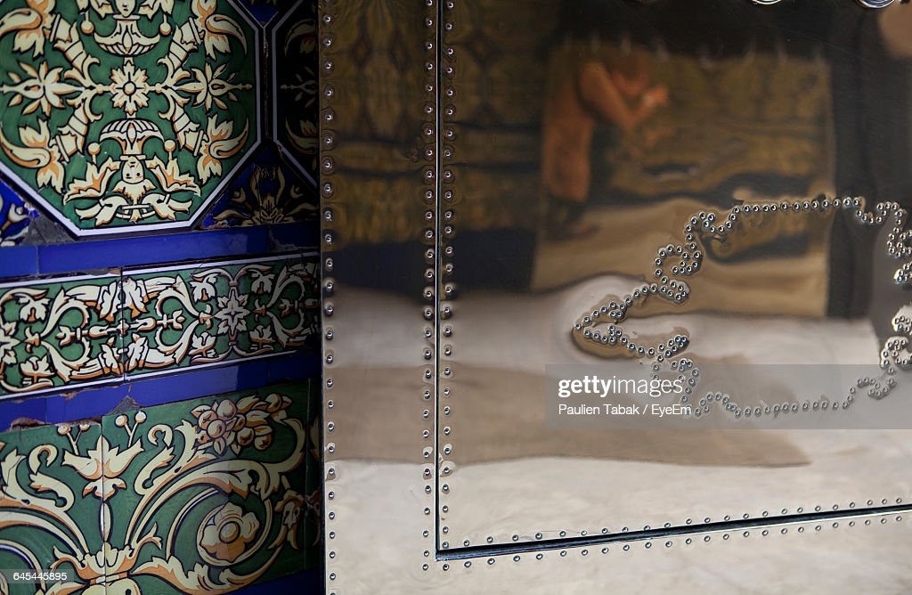 Reflection On Silver Ornate Against Pattern On Tile Wall : Stock Photo