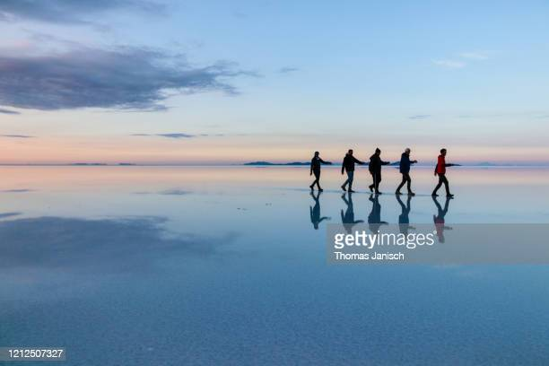 reflection on the salar de uyuni, bolivia - five people stock pictures, royalty-free photos & images