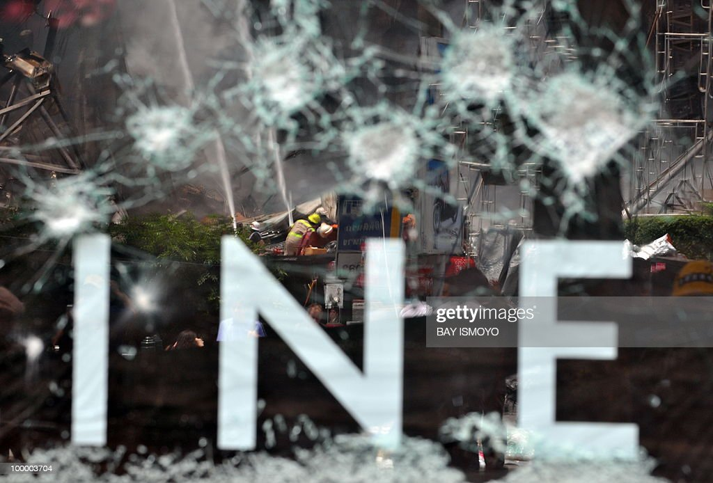 A reflection on the smashed glass of a shopping mall shows fire fighters extinguishing a smouldering building in downtown Bangkok on May 20, 2010. Thai police escorted thousands of protesters out of a Buddhist temple where they had cowered overnight after nine people were killed there in gunbattles. AFP PHOTO / Bay ISMOYO