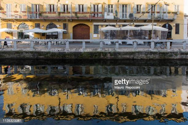reflection on the water canal and people walking on a street at the waterfront in il navigli, milan, italy. - navigli milano foto e immagini stock