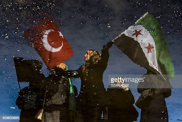 TOPSHOT A reflection on waste liquid shows a woman wawing Turkish and Free Syrian flags as an aid convoy to Aleppo organized by IHH Humanitarian...
