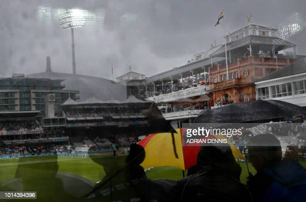 A reflection shows spectators huddled beneath umbrellas as rain stops play on the second day of the second Test cricket match between England and...