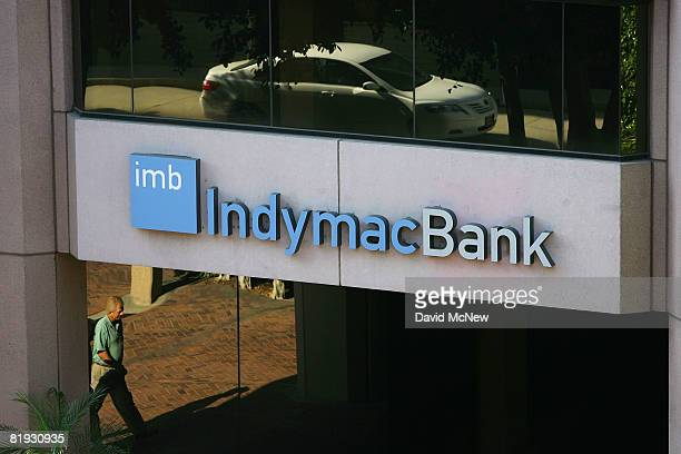 Reflections are seen in windows near an IndyMac Bank sign as hundreds of customers arrive to wait in line to get into an IndyMac Bank open for the...