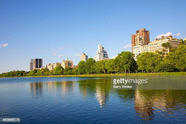 reflections in calm waters of reservoir, nyc - mount sinai hospital manhattan stock photos and pictures