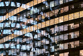 Reflections in glass office facade at dusk