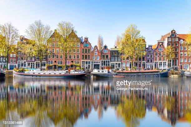 reflections in the morning on a canal of amsterdam, holland - amsterdam stock pictures, royalty-free photos & images