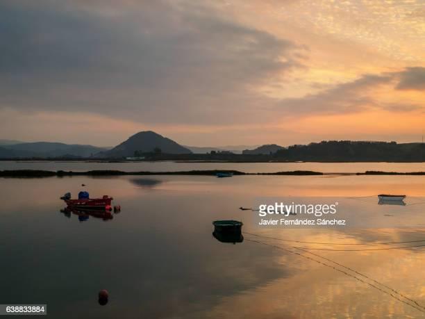 reflections in the water at sunset in the bay of santoña, cantabría, spain. - cantabria fotografías e imágenes de stock